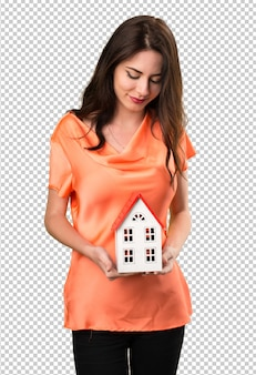 Belle jeune fille tenant une petite maison