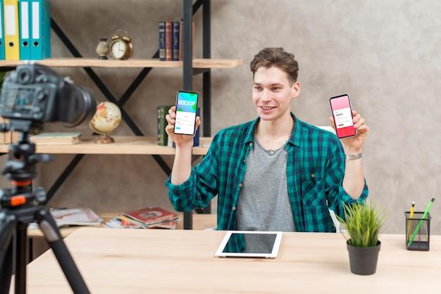 Blogger mid shot tenant des téléphones de maquette