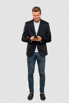 Blonde bel homme envoie un message avec le mobile