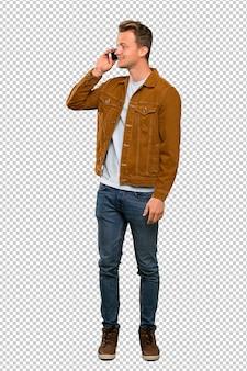 Blonde bel homme gardant une conversation avec le téléphone mobile