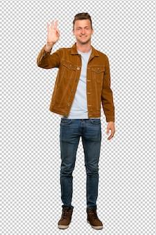 Blonde bel homme heureux et comptant trois avec les doigts