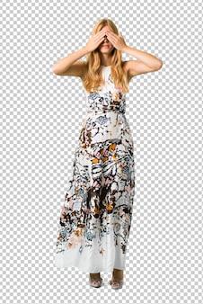 Blonde jeune fille vêtue d'une robe d'été couvrant les yeux par les mains. je ne veux pas voir quelque chose