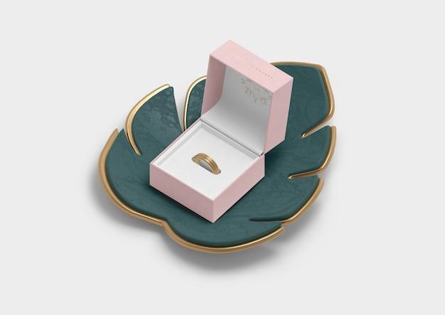 Boîte à bijoux ouverte pour bague et feuille de monstera