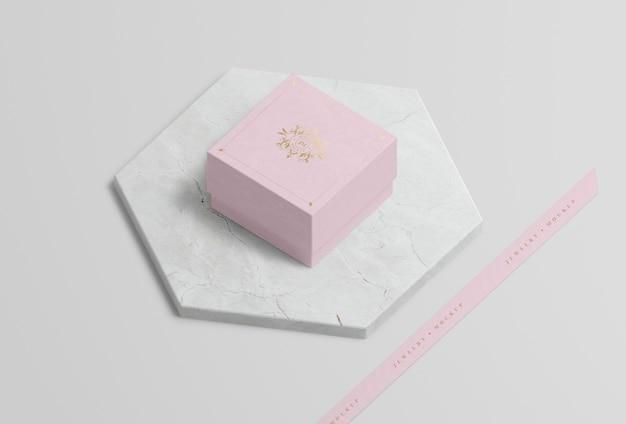 Boîte à bijoux rose sur marbre avec symbole doré