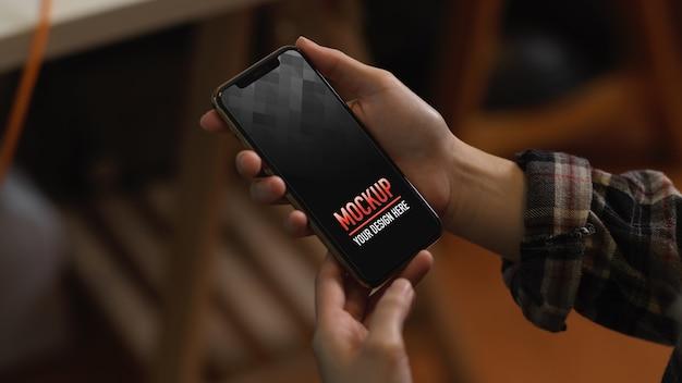 Bouchent la vue des mains féminines tenant le smartphone maquette