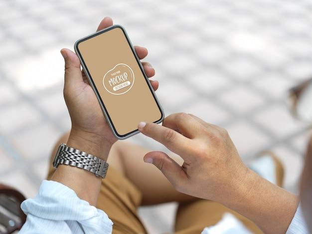 Bouchent la vue sur les mains tenant le smartphone avec maquette d'écran
