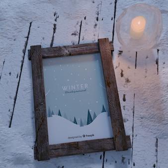 Bougie à côté du cadre avec thème hiver