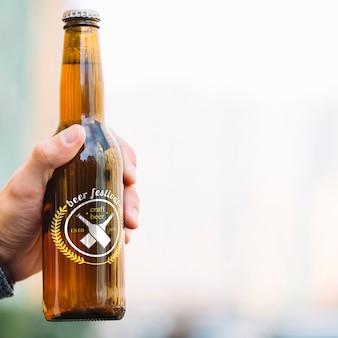 Bouteille de bière vue de face tenue par personne