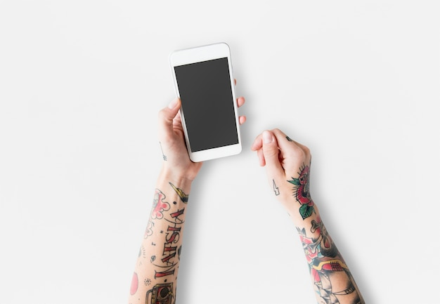 Bras avec des tatouages en utilisant un smartphone