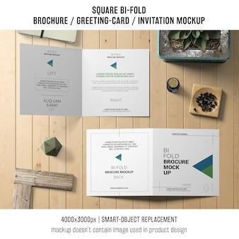 Brochure bi-fold carrée ou maquette de carte de voeux sur table en bois