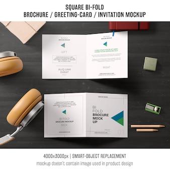 Brochure bi-fold carrée ou maquette de carte de voeux sur table