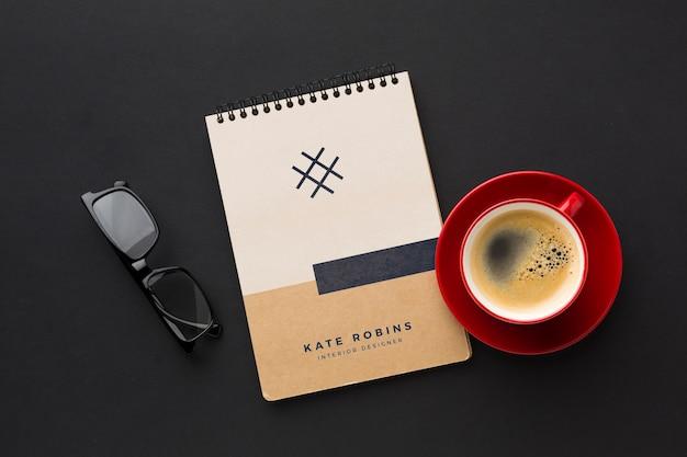 Bureau avec café, lunettes et maquette de cahier