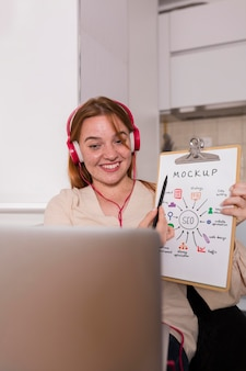 Businesswoman montrant sa maquette de presse-papiers lors d'une vidéoconférence