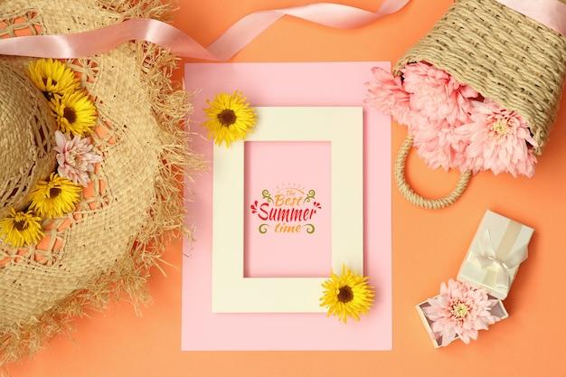 Cadre de maquette estival plat avec chapeau de paille et panier de fleurs