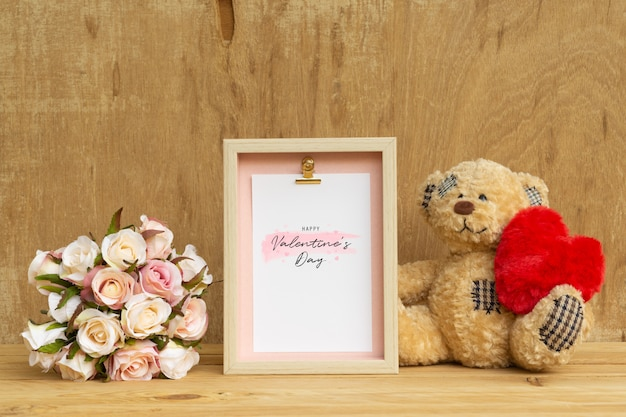 Cadre et mignon ours tenant une maquette de coeur rouge