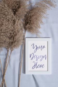 Cadre photo avec maquette de carte papier vierge près de l'herbe sèche de la pampa sur textile de couleur neutre bleu