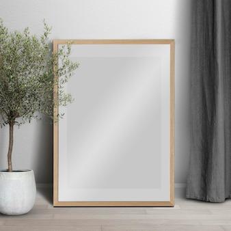 Cadre photo maquette psd se penchant dans un intérieur minimaliste de décoration de salon