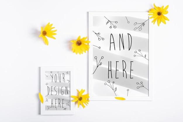 Cadre photo vide blanc maquette avec fleur jaune sur blanc, pose à plat