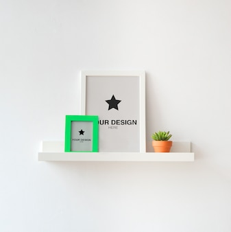 Cadres photo maquette (couleur modifiable) sur étagère blanche avec plante
