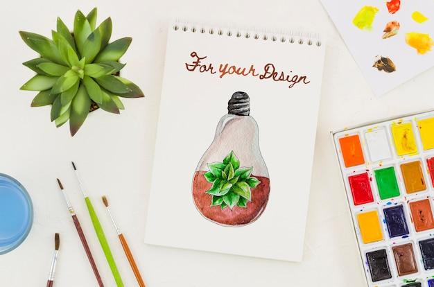 Cahier avec dessin réaliste et palette acrylique à côté