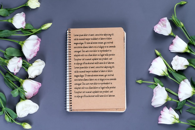 Cahier vide ouvert et bouquet de fleurs eustoma sur maquette en papier foncé