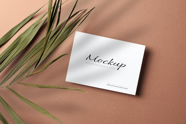 Carte d'invitation ou flyer, maquette stationnaire avec feuille de palmier nature sèche sur papier beige