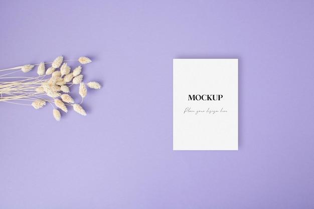 Carte d'invitation de maquette avec de l'herbe sèche sur fond violet