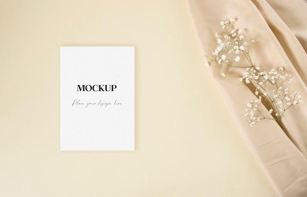 Carte d'invitation de mariage maquette avec gypsophile blanc et tissu nude sur fond beige