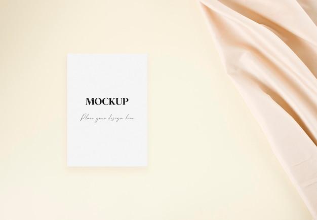 Carte d'invitation de mariage maquette avec tissu nude sur fond beige