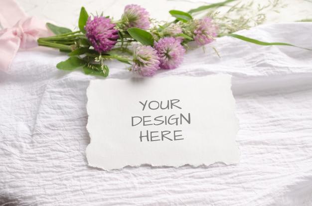 Carte de maquette de mariage avec des bords dentelés avec des fleurs roses et de délicats rubans de soie sur fond blanc.