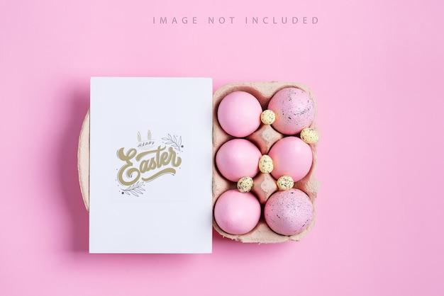 Carte postale de maquette avec des oeufs roses peints et une carte en papier. concept de joyeuses pâques. vue de dessus.
