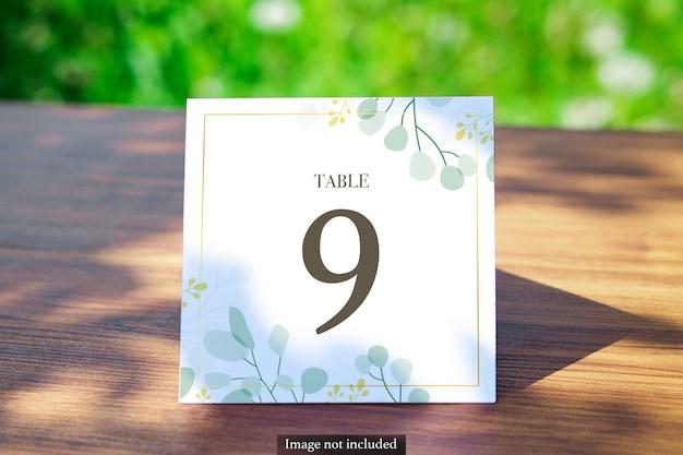 Carte de table carrée sur la maquette extérieure floue de verdure