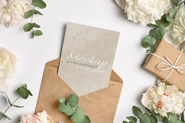 Carte de voeux ou maquette d'invitation avec enveloppe, boîte-cadeau et fleurs de pivoine blanche avec des brindilles d'eucalyptus