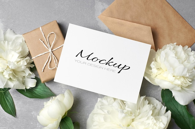 Carte de voeux ou maquette d'invitation avec enveloppe, boîte-cadeau et fleurs de pivoine blanches sur fond gris