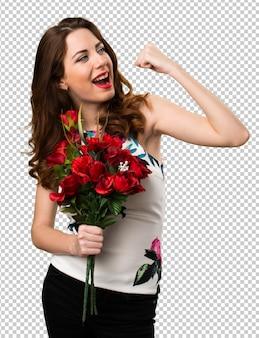Chanceux belle jeune fille tenant des fleurs