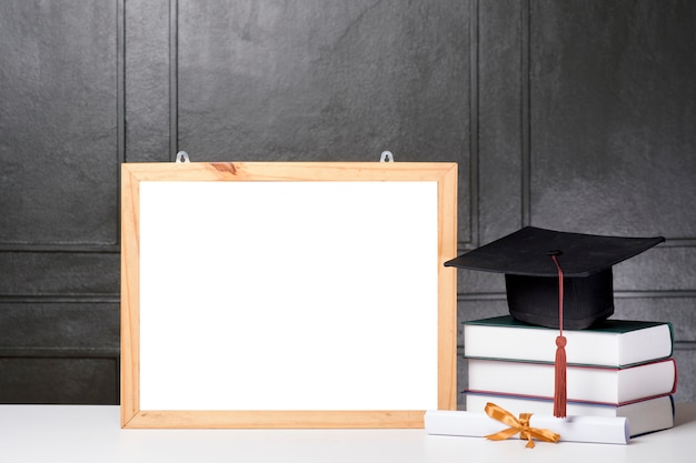Chapeau de graduation et livre avec maquette de cadrecas de graduation et livre avec maquette de cadre