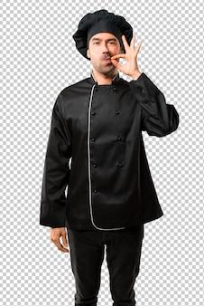 Chef homme en uniforme noir montrant des signes de fermeture de la bouche et du silence