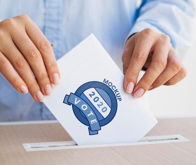 Close-up personne mettant la maquette de bulletin de vote dans la boîte
