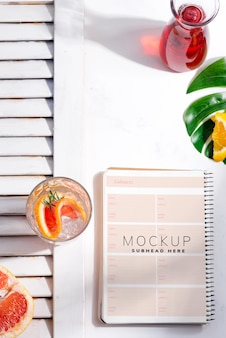 Cocktail maison d'été froid dans un verre avec une tranche de pamplemousse et un carnet de notes en papier
