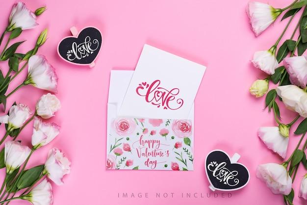 Composition de cadre avec des fleurs d'eustoma roses, maquette d'enveloppe et coeurs de tableau