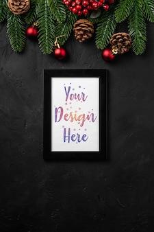 Composition de noël avec cadre photo vide. ornement coloré, pommes de pin et décorations d'aiguilles de sapin. maquette de modèle de carte de voeux