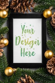 Composition de noël avec cadre photo vide. ornement doré, pommes de pin et décorations en aiguilles de sapin. maquette de modèle de carte de voeux