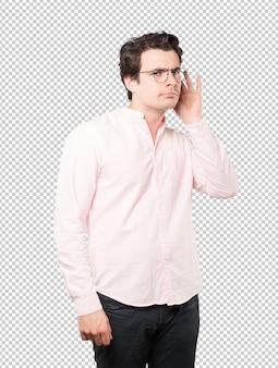 Concentré de jeune homme faisant un geste d'essayer d'entendre quelque chose