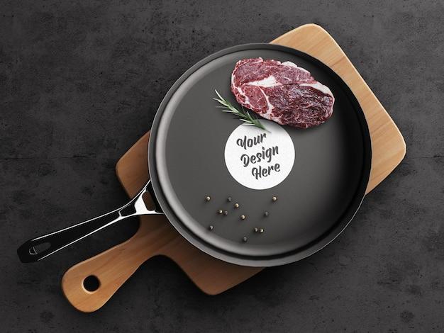 Concept de cuisine de maquette de logo de restaurant avec un steak sur une poêle à frire et des outils de cuisine en planche à découper en bois