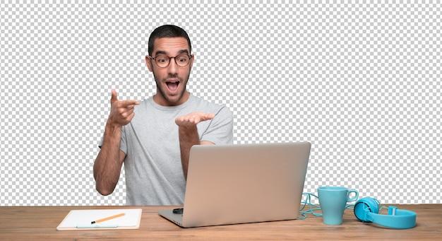 Confiant jeune homme assis à son bureau avec un geste de montrer quelque chose