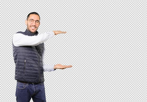 Confiant jeune homme faisant un geste de tenir quelque chose avec ses mains