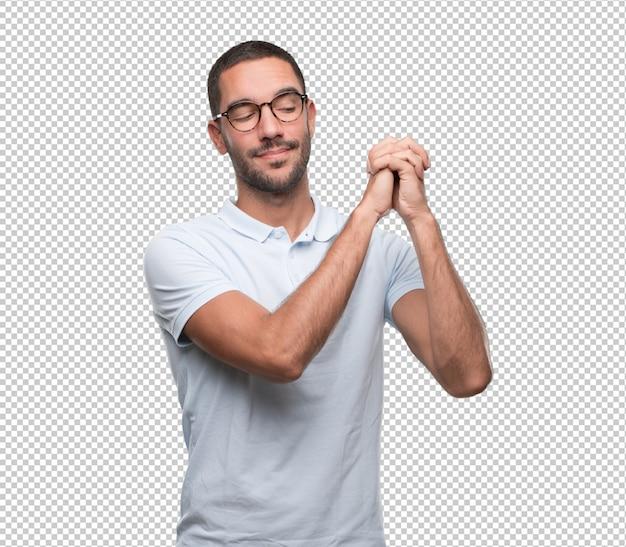 Confiant jeune homme faisant un geste de l'unité avec ses mains