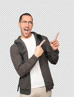 Cool étudiant pointant avec ses doigts