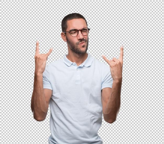 Cool jeune homme fait un geste de rock avec ses mains