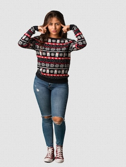 Corps complet jeune femme portant un maillot de noël faisant un geste de concentration